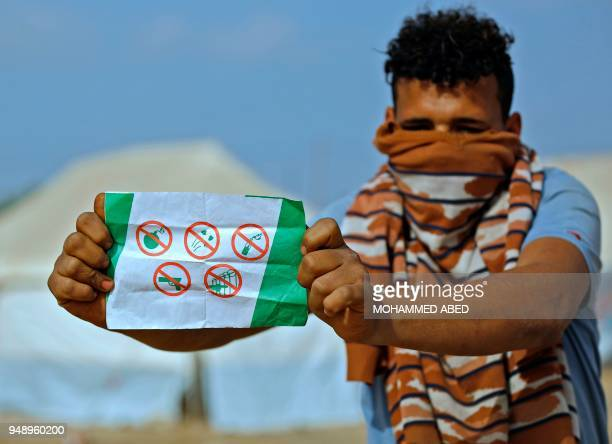Palestinian man displays a leaflet that was airdropped by Israeli army over Gaza calling on residents of the coastal Palestinian territory not to use...
