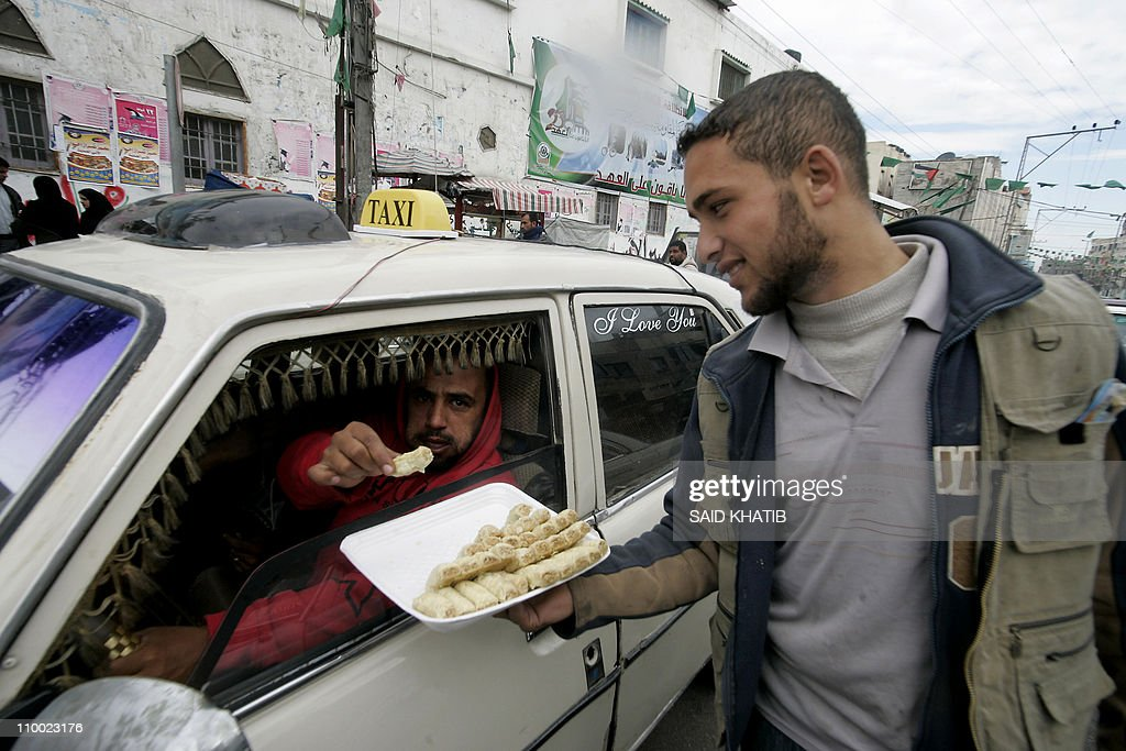 A Palestinian man distributes sweets in : News Photo