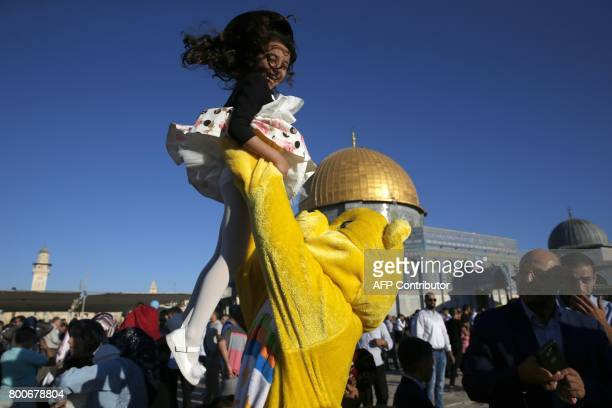 A Palestinian man dressed in a bear outfit plays with a girl as Muslims gather for the morning Eid alFitr prayer near the Dome of Rock at the AlAqsa...
