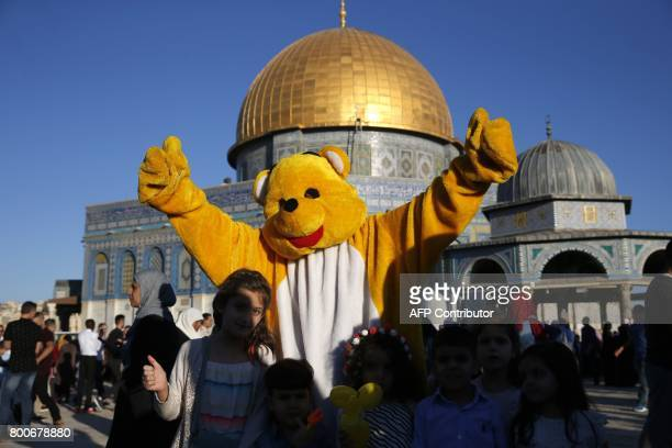A Palestinian man dressed in a bear outfit plays with children as Muslims gather for the morning Eid alFitr prayer near the Dome of Rock at the...