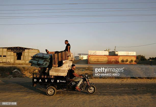 Palestinian man drives a three wheeler loaded with sofas and mattresses on August 21 2016 in Beit Hanun in the northern Gaza Strip / AFP / MOHAMMED...