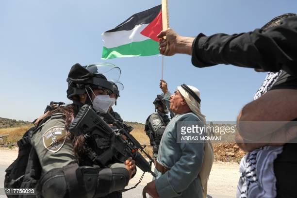 Palestinian man facing Israeli forces waves a national flag during a protest against Israel's plan to annex parts of the occupied West Bank, near the...