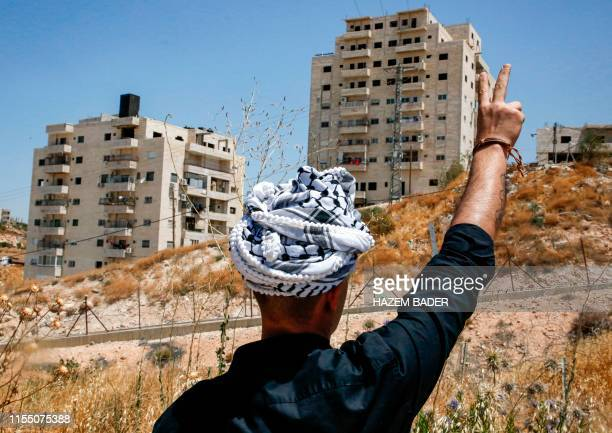 A Palestinian man flashes the victory gesture during a demonstration in the Palestinian village of Beit Sahur in the occupied West Bank on July 11...
