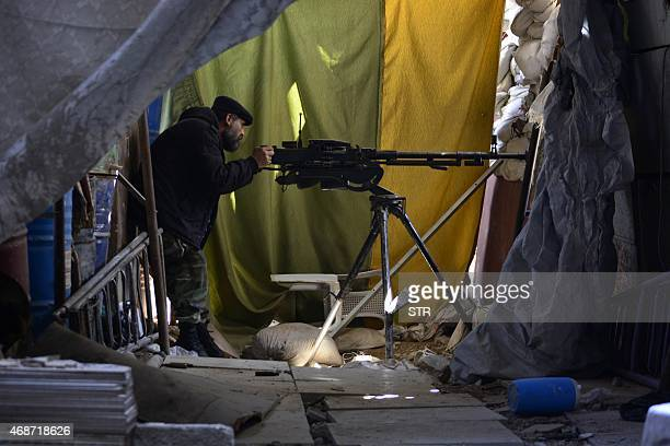 A Palestinian man guards a post in Yarmuk Palestinian refugee camp in the Syrian capital Damascus on April 6 2015 Around 2000 people have been...