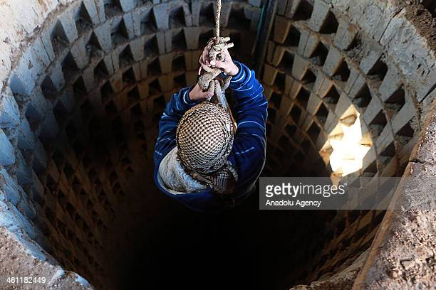 Palestinian man hangs on the rope in Gaza city Gaza on January 7 2014 Egyptian forces destroy and flooded some of the tunnels with sewage beneath the...