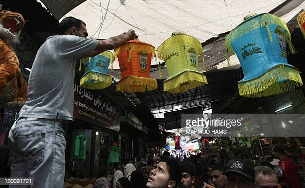 A Palestinian man hangs paper lanterns outside his shop ahead of the Muslim holy fasting month of Ramadan at AlZawiya market in Gaza City on July 30...
