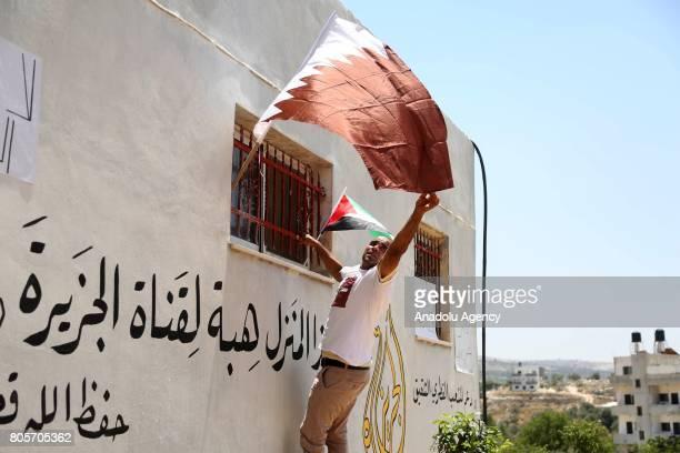 Palestinian man hangs Qatari flag to the window of a house after Palestinian farmer Ayid Burnat donates his house to Dohabased Al Jazeera Television...