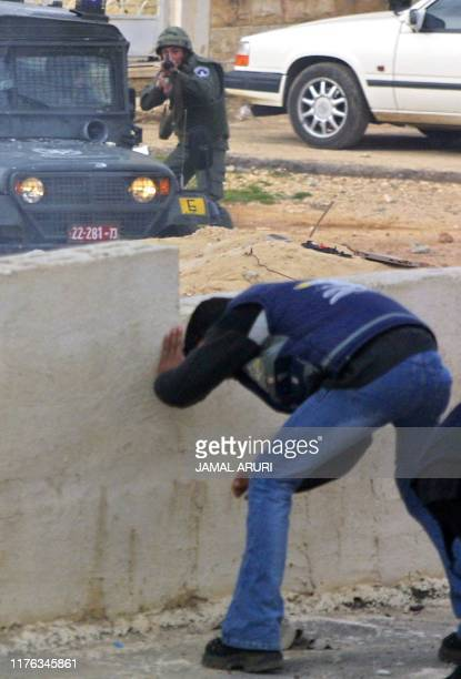 Palestinian man hides behind a wall as an Israeli soldier aims at stone-throwers during clashes in the West Bank town of Ramallah 28 December 2001....