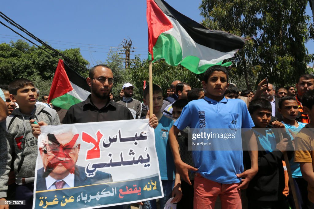 Palestinian man hold signs as supporters of Hamas, Jihad Islamic and Al Ahrar movement gather to protest against President of the State of Palestine and Palestinian National Authority Mahmoud Abbas and to demand an end to the Israeli blockade of the Gaza Strip on 2 May 2017 , on May 2 in Gaza.