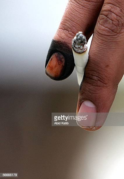 Palestinian man holds a cigarette with his inked finger proving that he has voted at a polling station in the UN school Alef which is being used as...
