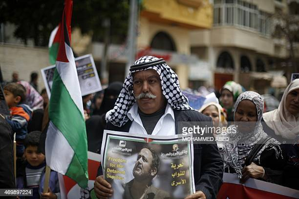 A Palestinian man holds a portrait of Fatah leader Marwan Barghuti who is imprisoned in an Israeli jail during a protest marking Palestinian...