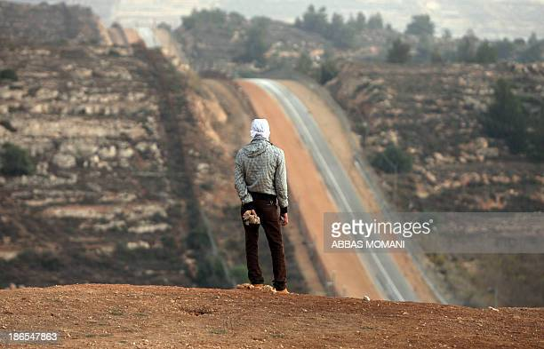 A Palestinian man holds a stone during clashes close to the Israeli military prison of Ofer near the village of Betunia in the West Bank on November...