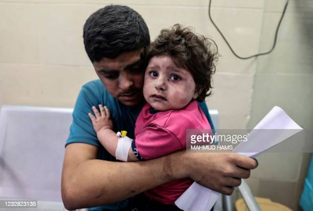 Palestinian man holds an injured girl awaiting medical care at al-Shifa hospital, after an Israeli air strike in Gaza city, on May 11, 2021.