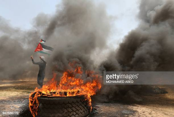 Palestinian man holds his national flag as others burn tyres to protect themselves from shots of Israeli soldiers at the Israel-Gaza border, east of...