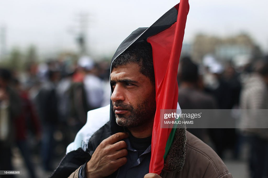A Palestinian man holds his national flag over his head as he takes part in a rally marking Land Day in Beit Hanun in the northern Gaza Strip on March 30, 2013. Land Day commemorates the death of six Arab Israeli protesters at the hands of Israeli troops during mass protests in 1976 against plans to confiscate land in Galilee.