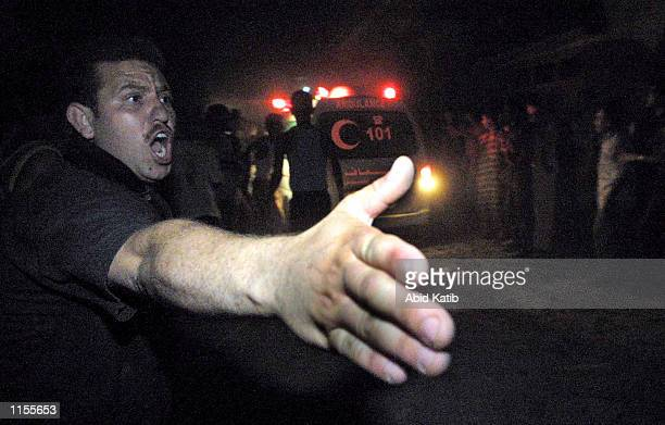 Palestinian man holds out his hand as an ambulance drives by after a late night Israeli missile strike July 23 2002 in Gaza City Gaza Hamas leader...