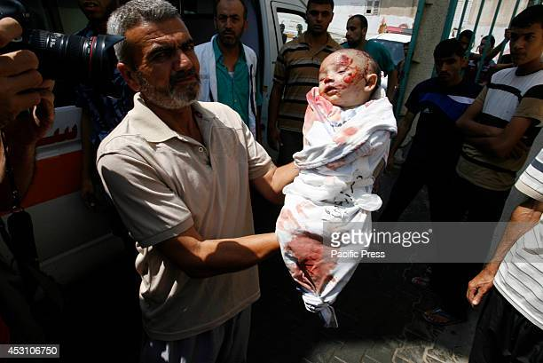 Palestinian man holds the body of two month old Noor al-Saidy, killed during attacks on the Gaza Strip, during her funeral in Rafah, in the southern...