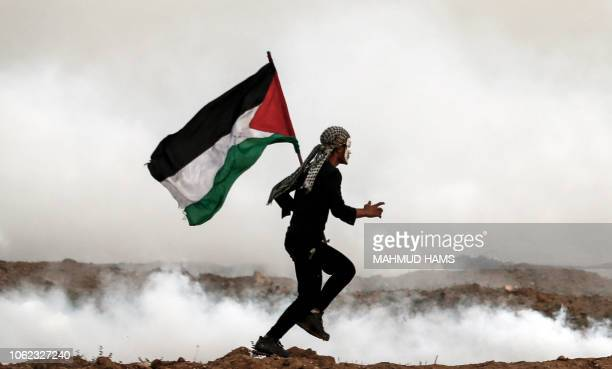 A Palestinian man holds the national flag as he runs through teargas during a protest on November 16 on the eastern outskirts of Gaza City near the...