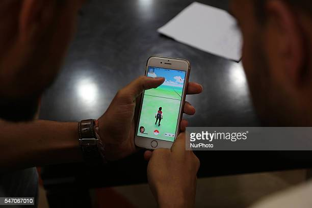 Palestinian man holds up her cell phone as she plays the Pokemon Go game in gaza city, July 13, 2016.