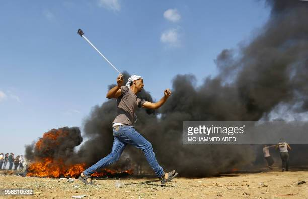 Palestinian man hurls a stone during clashes with Israeli forces on May 15, 2018 near the border fence with Israel east of Jabalia in the central...