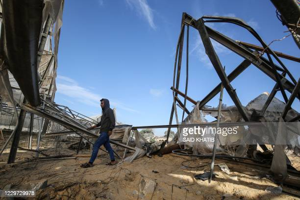 A Palestinian man inspects the damage at the site of an Israeli air strike in Khan Yunis town the southern Gaza Strip November 22 2020 A rocket was...