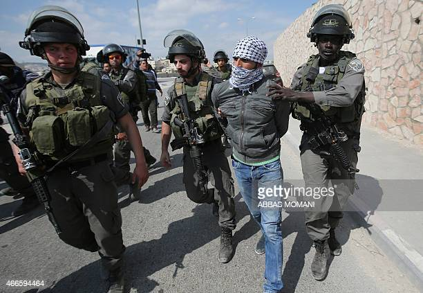 A Palestinian man is detained by members of the Israeli security forces during clashes following a march attended by Palestinian Israeli and foreign...