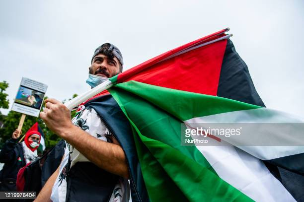 A Palestinian man is giving Palestinian flags to the people during the demonstration in solidarity with Palestine at the Museumplein in Amsterdam...