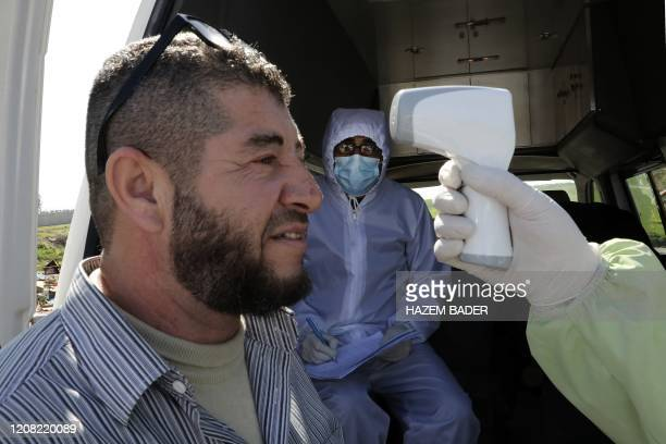 Palestinian man just released from an Israeli jail gets his temperature checked as he returns home via the Mitar checkpoint in the occupied West Bank...
