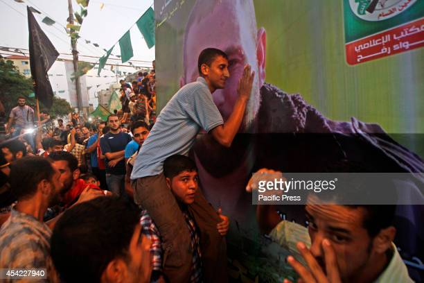 Palestinian man kissing the picture of Hamas senior leader Raed al-Attar who was killed within fighting in the Gaza strip.