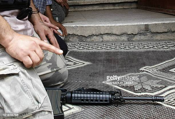 A Palestinian man kneels with his automatic rifle at his side during Friday noon prayers in the Ain alHelweh Palestinian refugee camp in the southern...