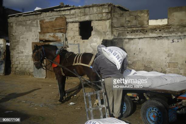 Palestinian man loads a horsepulled cart with food donations outside the United Nations food distribution centre in Gaza City on January 15 2018...
