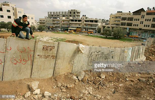 Palestinian man looks out for Israeli soldiers as he attempts to climb over the wall from Abu Dis West Bank on March 26 2006 into East Jerusalem...