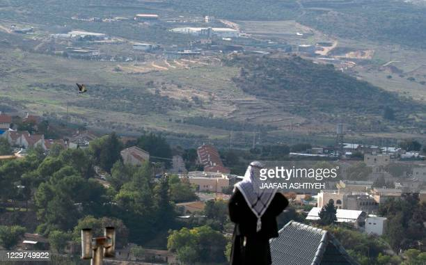 A Palestinian man looks towards the Israeli settlement of Shavei Shomron built next to the Palestinian village of Naqoura west of Nablus in the...