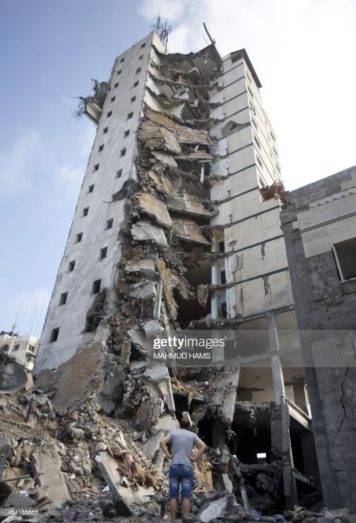A Palestinian man looks up at the remains of an Italian apartment block that was destroyed by an Israeli air strike overnight in Gaza City on August 26, 2014. An Israeli air raid in Gaza killed two Palestinians as Israel pursued its campaign to stop rocket fire by Hamas militants from the enclave, medics said.