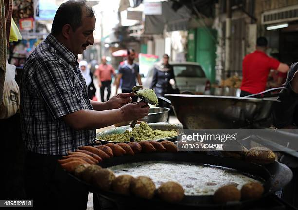 Palestinian man makes falafel a traditional dish consisting of fried chickpeas on a street in the West Bank city of Nablus on September 19 2015 AFP...