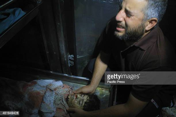 Palestinian man mourn at the body of young Palestinian at a morgue in the Al-Shifa Hospital after an Israeli air attack in Gaza City, the death toll...
