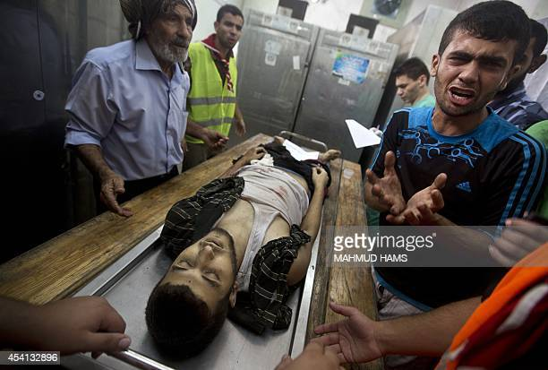 A Palestinian man mourns as he stands next to the body of a relative that was killed by an Israeli air strike at a hospital morgue in Beit Lahia in...