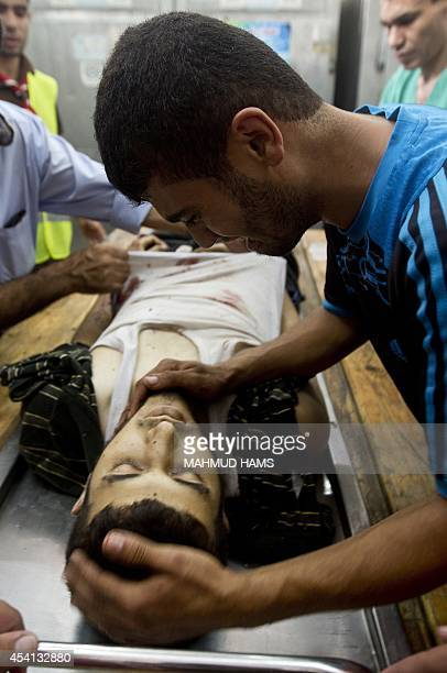 A Palestinian man mourns as he touches a relative that was killed by an Israeli air strike at a hospital morgue in Beit Lahia in the northern Gaza...