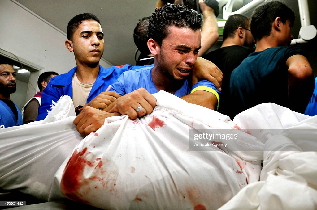 A Palestinian man mourns over the body of Palestinian who were killed in an Israeli air strike targeting the Sheik Radwan cemetery, in the morgue of the Shifa hospital on August 21, 2014. Four Palestinians named Muhammed, Rami Ebu Nehal, Heysem Tafis and Abd Suveyh were killed in an Israeli airstrike targeting the Sheik Radwan cemetery in northwestern of Gaza Strip. According to Health Ministry spokesman Ashraf al-Qodra the latest fatalities, he said, bring the total number of Palestinians killed in relentless Israeli attacks on the Gaza Strip to 2072 since hostilities began on July 7.