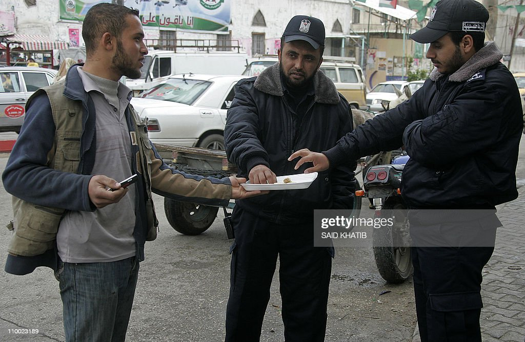 A Palestinian man offers sweets to Hamas policemen in the streets of the southern Gaza Strip town of Rafah on March 12, 2011 to celebrate an attack which killed five Israeli settlers at the Itamar settlement near the West Bank city of Nablus.
