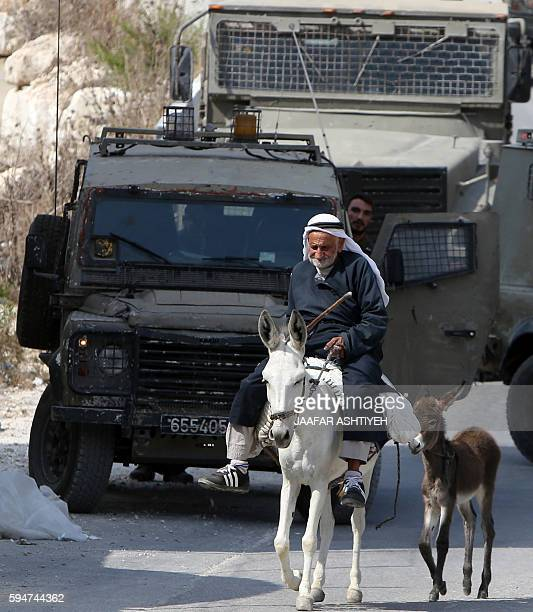 A Palestinian man on his donkey turns around in front of Israeli soldiers at an entrance of the northern West Bank village of Madama on August 24...
