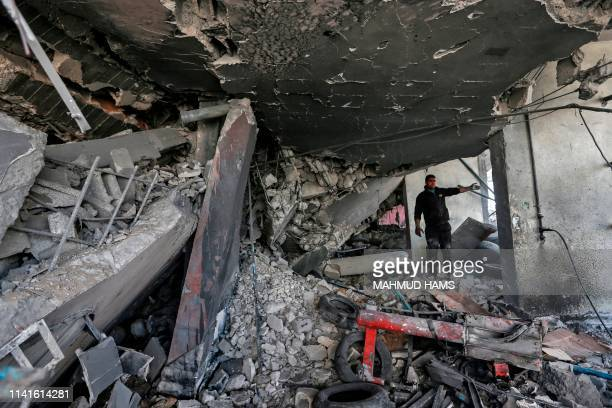 Palestinian man on May 6 checks the damaged caused by Israeli airstrikes inside a buidling in Gaza City. - Palestinian leaders in Gaza agreed a...