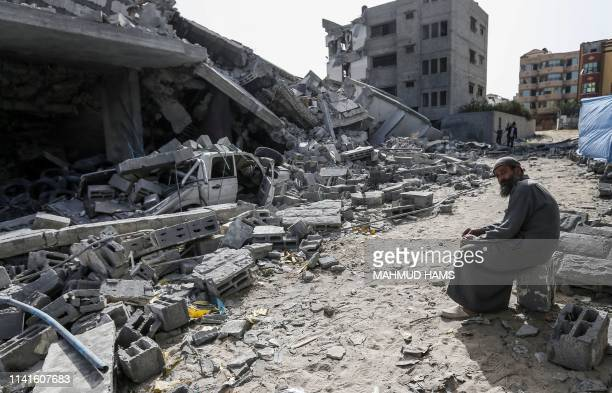 Palestinian man on May 6 sits amidst the rubble of a building that was destroyed during Israeli airstrikes on Gaza City. - Palestinian leaders in...