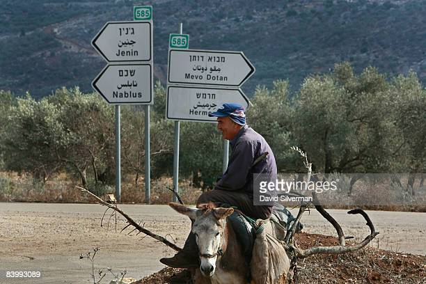 Palestinian man passes a roadsign point to the Palestinian cities of Jenin and Nablus to the left and the Israeli settlements of Mevo Dotan and...
