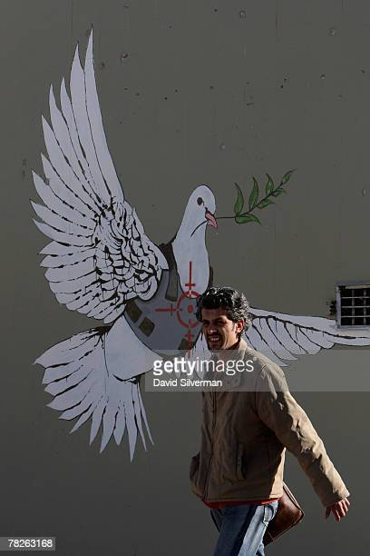 Palestinian man passes a wall painting by elusive British graffiti artist Banksy December 5 2007 on a shop wall in the biblical city of Bethlehem in...
