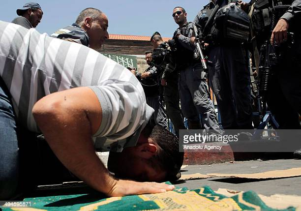 Palestinian man performs Friday prayers on the streets outside the AlAqsa Mosque compound after Israeli police barred under 45 years Muslim...