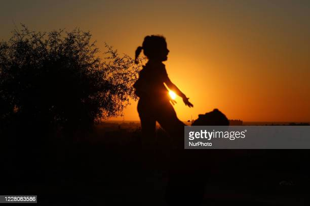 Palestinian man plays with his daughter during sunset in the central Gaza Strip, on August 17, 2020.