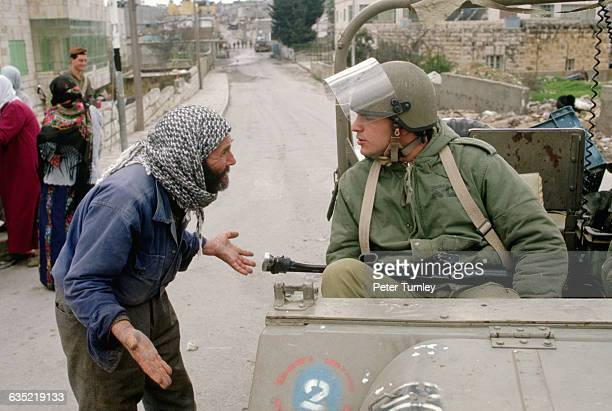 A Palestinian man pleads with an Israeli soldier for the release of a boy being held in Am'Ari camp