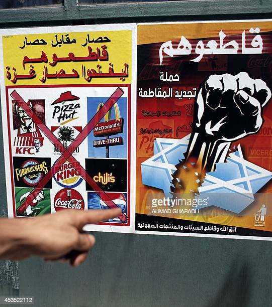 A Palestinian man points at posters calling people to boycott Israeli products following the latest war between Hamas militants in the Gaza Strip and...