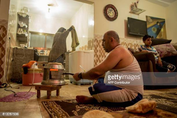 A Palestinian man prepares bread as his wife washes clothes during the few hours of mains electricity they receive every day on July 11 at the...